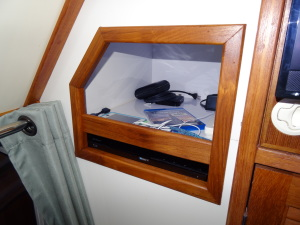"""We added a storage area right next to the TV in the main saloon. Below is the DVD Player and above is a storage area wired as a """"Charging Station."""""""